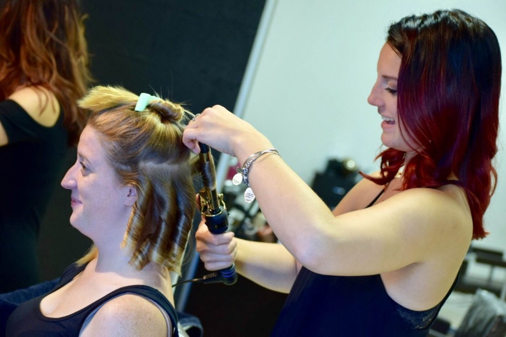 Smiling woman having her hair curled by stylist