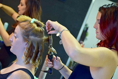 Stylist using curling iron on blond woman