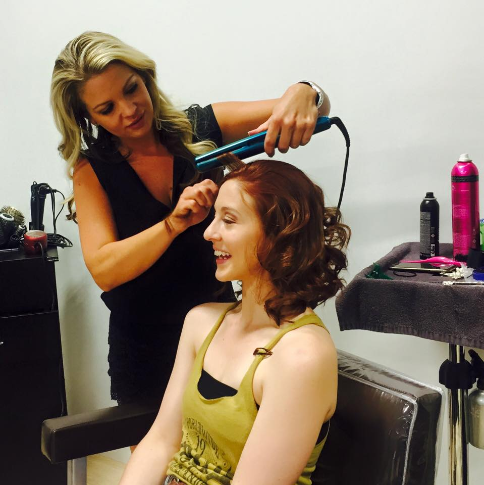 Michelle using curling iron on a client