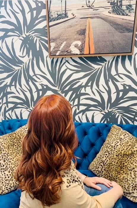 Red headed woman sitting looking at photo on wall