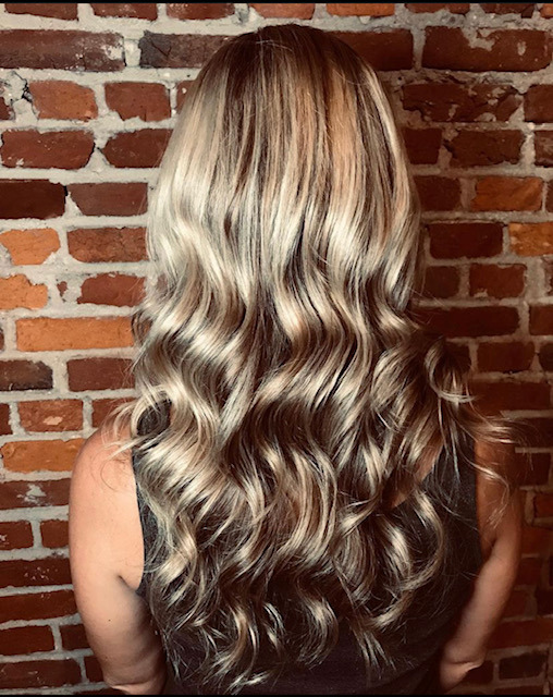 Wavy dirty blond hair with brick background