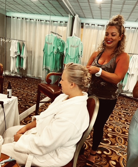 Lady braiding hair of other lady in white robe
