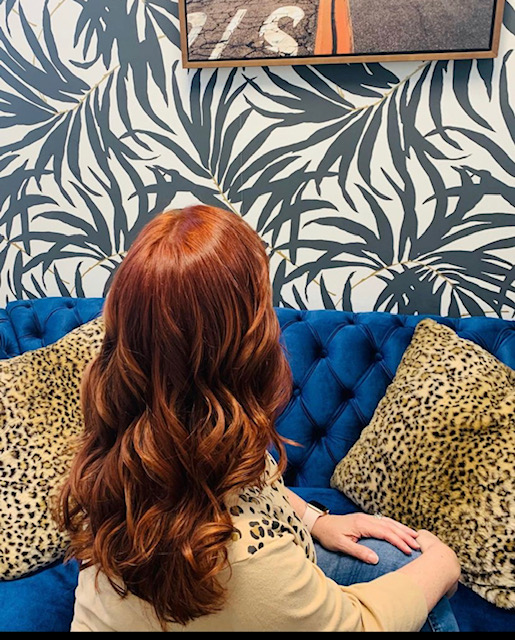 Lady with red hair sitting on couch
