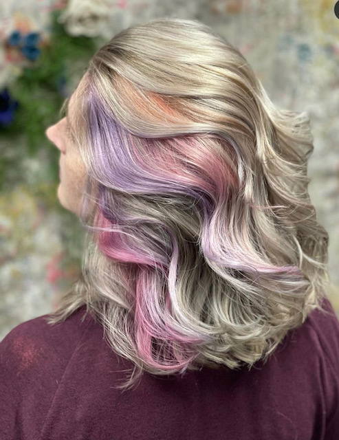 Lady waving her blond hair with pink and purple streaks