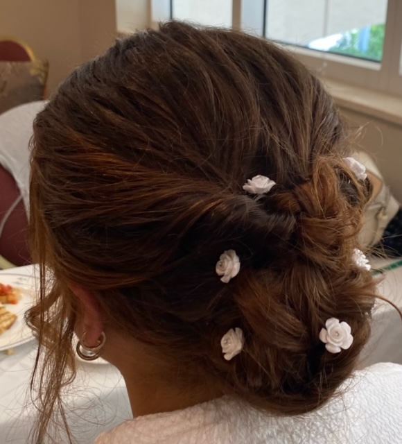 Light brown hair up in braided bun with flower clips