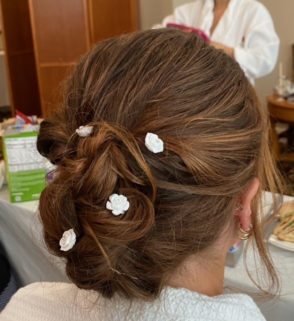 Light brown hair braided with flower clips