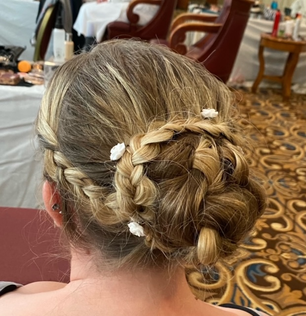 Dirty blond hair braided in a bun with flower clips