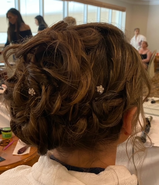 Light brown hair braided and up with flower clips