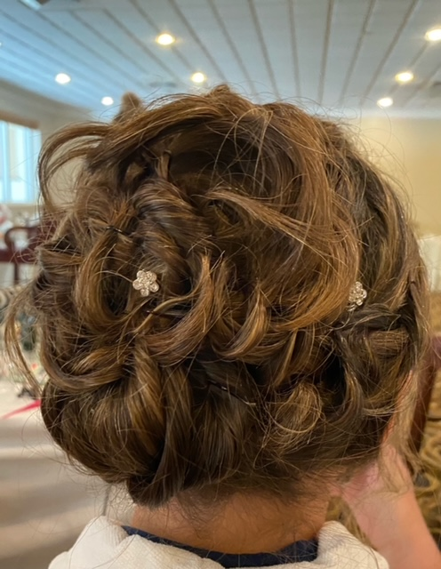 Brown hair up in intricate bun and flower clips