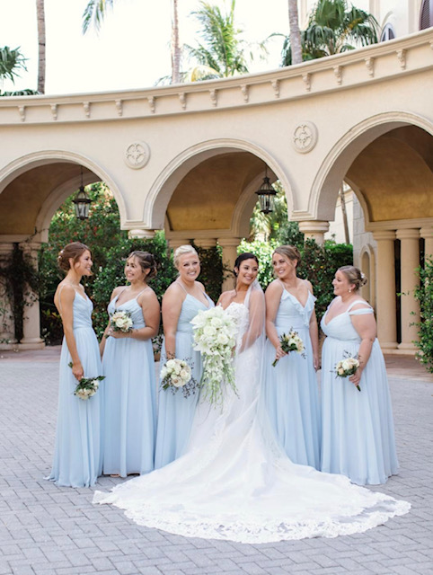 Bride standing inbetween bridesmaids outside