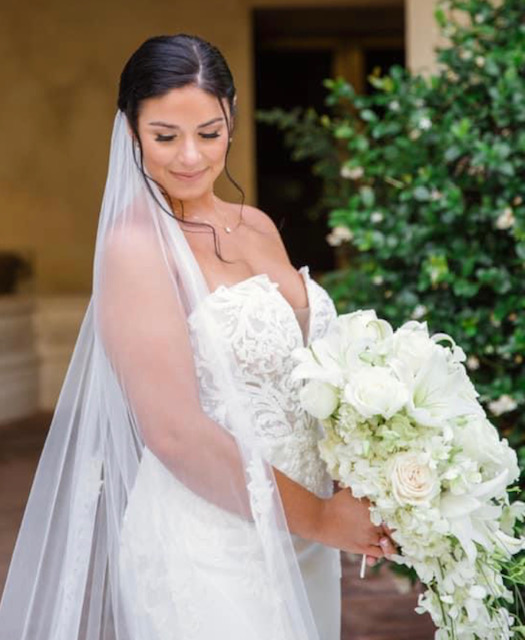 Bride looking at floor while holding large white bouquet