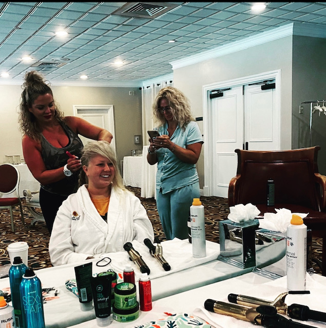 Bride's hair getting done at large white table
