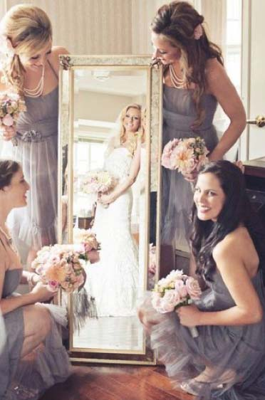 Bridesmaids standing around mirror reflecting image of bride